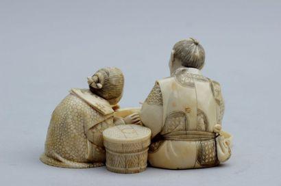 OKIMONO en ivoire représentant un couple autout d'un ibashi, l'homme tenant un bol...