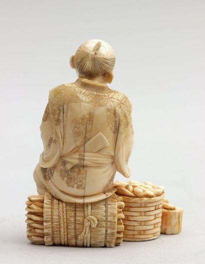 OKIMONO en ivoire représentant un paysan assis sur un fagot tenant son matériel...