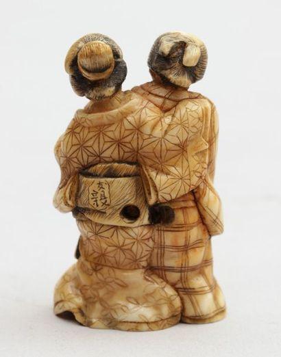 NETSUKE en ivoire représentant un couple, une Oiran ( courtisane de haut rang ),...
