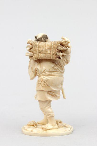OKIMONO en ivoire représentant un vigneron portant un fagot de sarments et une grappe...