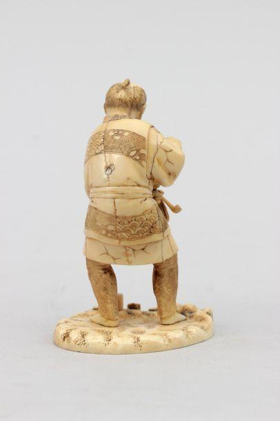 OKIMONO en ivoire représentant un paysan tenant son nécessaire à fumer, signé Seishi....