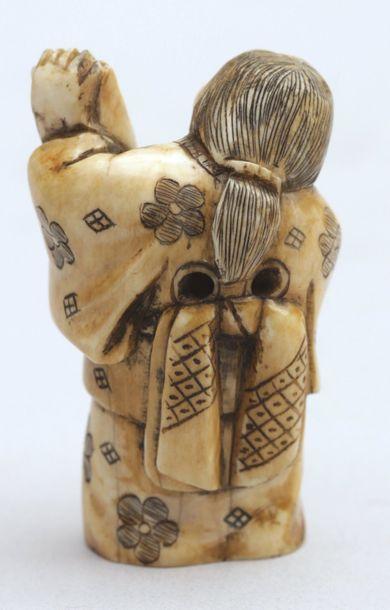 NETSUKE en ivoire représentant Okame déroulant un kakemono sur lequel est dessiné...