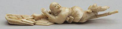OKIMONO en ivoire représentant un paysan allongé tenant une serpe reposant sur un...
