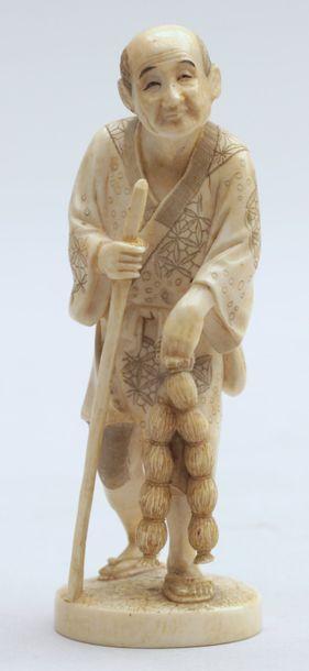 OKIMONO en ivoire représentant un paysan appuyé sur un bâton tenant deux bottes...