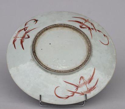 PLAT sur talon en porcelaine à décor émaillé polychrome de fleurs et frises et objets...