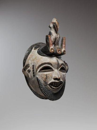 IDOMA, Nigéria  Masque barbu couvert de kaolin, surmonté d'un oiseau perché entre...