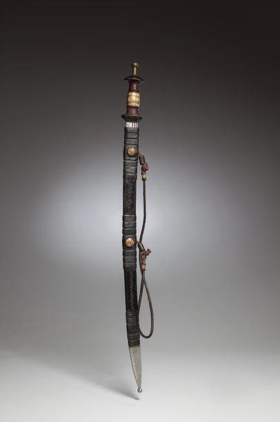 MALINKE, Guinée  Epée en fer forgé dont le fourreau en cuir patiné est soigneusement...