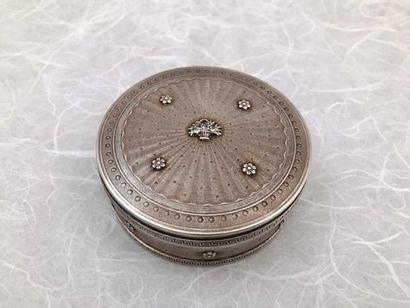 BOITE EN ARGENT Boîte circulaire en argent guilloché à décor de fleurettes, frise...