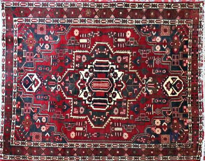 IRAN Woollen carpet with yn decoration central polygonal medallion inscribed in...