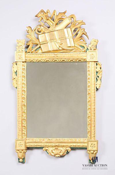 Miroir en bois sculpté et doré, il est surmonté...