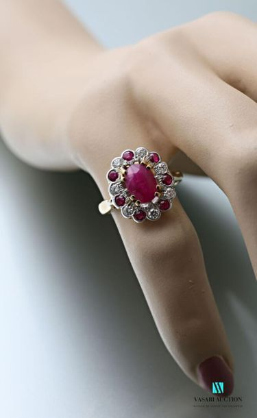 Two-tone 750 thousandths gold ring set with an oval-shaped unheated ruby calibrating...