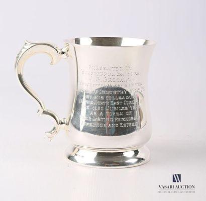 Mug en métal argenté posant sur une base...