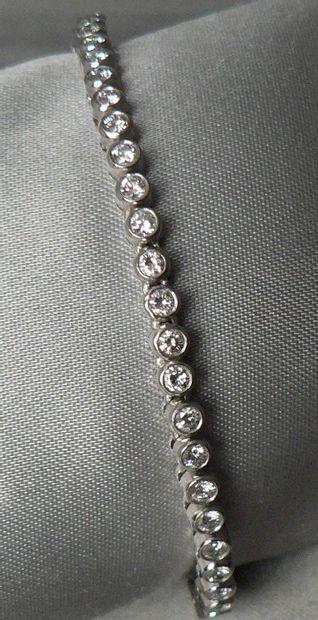 Bracelet en or gris, orné d'une ligne de brillants, en serti clos, de 3 carats environ. Poids...