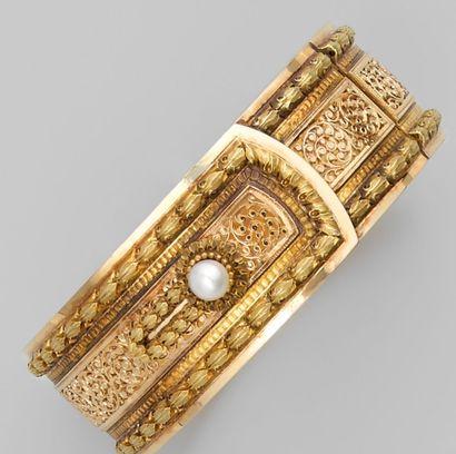 Bracelet rigide ouvrant du 19° en or rose et en or jaune, ajouré d'enroulement,...