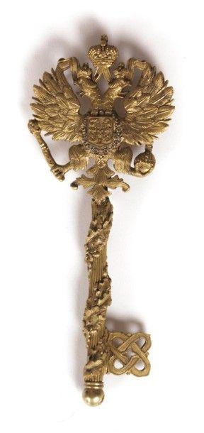 Clef en bronze doré et sculpté présentant...