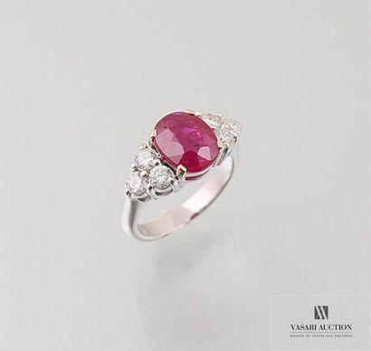 Bague en or gris ornée d'un rubis taille ovale calibrant 3,55 carats environ épaulé...