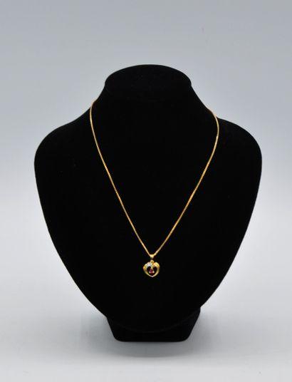 Pendentif coeur centré d'un rubis en or jaune et gris 750 millièmes, et sa chaîne...