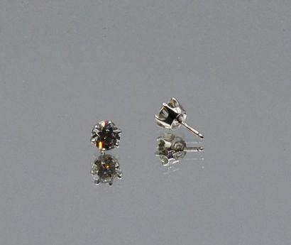 Paire de boutons d'oreilles en or gris, chacune sertie d'un diamant rond de taille...