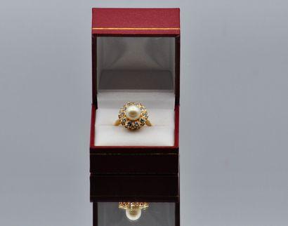 Bague marguerite en or 750 millièmes centrée d'une perle dans un entourage de diamants....