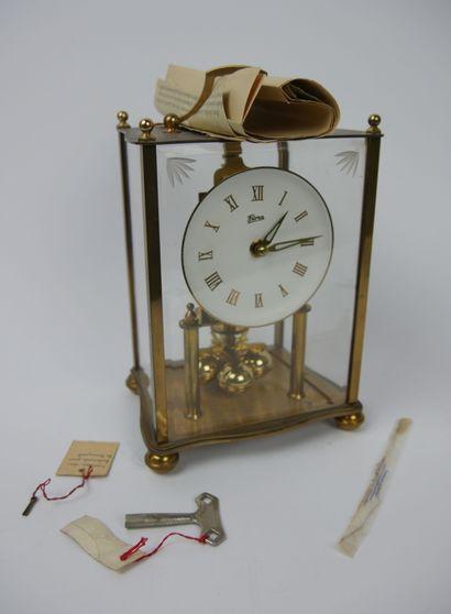FLORA  Pendule de salon en laiton doré et plexiglas, le cadran peint en blanc à...