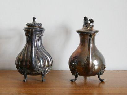 Deux théières en métal argenté et bois noirci. La première reposant sur un piètement...