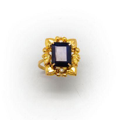 Bague en or 18k ornée d'un saphir pesant environ 8 ct. entouré de deux petits diamants...