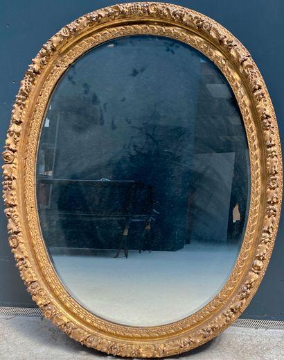 Miroir ovale en bois doré à décor en relief...