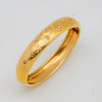 Bracelet rigide en or à décor gravé de fleurs...