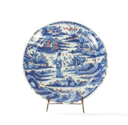 Rouen  Assiette en faïence à décor bleu et rouge de deux Chinoises tenant des fleurs...