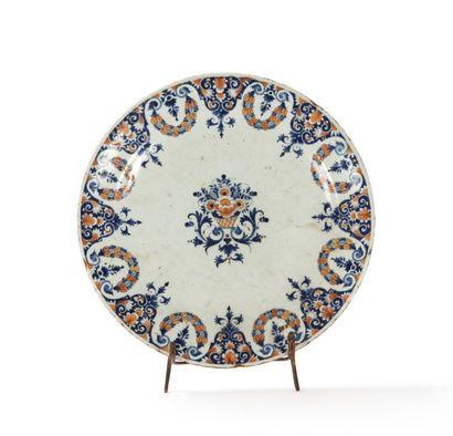Rouen  Assiette à décor bleu et rouge au centre d'une corbeille de fleurs sur des...
