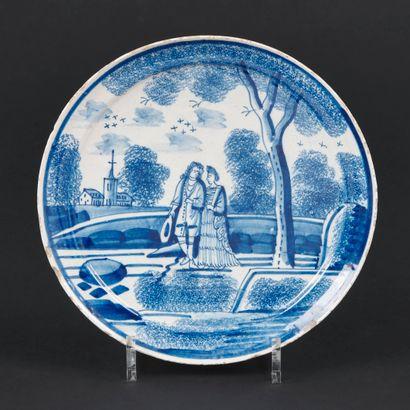 Delft  Assiette en faïence à décor en camaïeu bleu en plein d'un couple dans un...