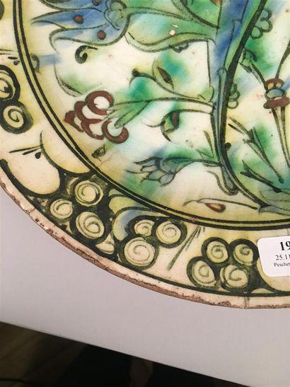Iznik Plat rond en céramique siliceuse à glaçure plombifère à décor polychrome d'une...