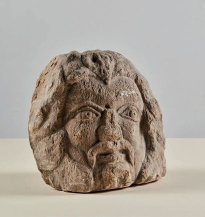 Head of divinity (?) in carved limestone. Bearded and mustached man with a pointed...