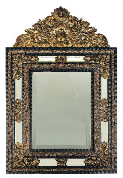 Miroir à fronton en ébène et cuivre repoussé,...