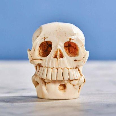 Crâne en ivoire sculpté portant un lézard....