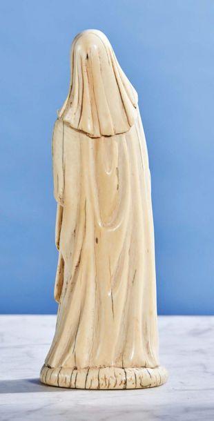 Sainte Religieuse en ivoire sculpté en rondebosse. Debout, elle tient un livre fermé...