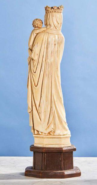 Vierge à l'Enfant en ivoire sculpté en ronde-bosse. Sur un socle à pans en bois...