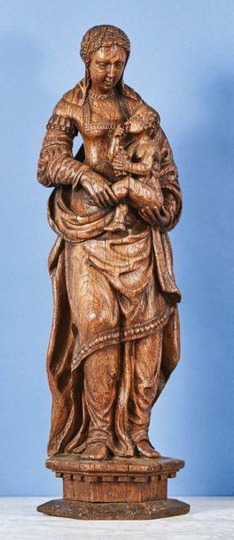 Vierge à l'Enfant au raisin en chêne sculpté en ronde-bosse. Debout, la Vierge porte...