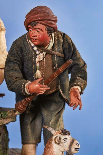 Crèche en bois sculpté et polychromé, en tissus et divers matériaux. Au centre,...
