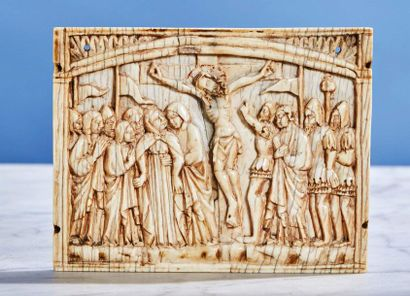 Central plaque of a carved ivory triptych representing the Crucifixion with red...