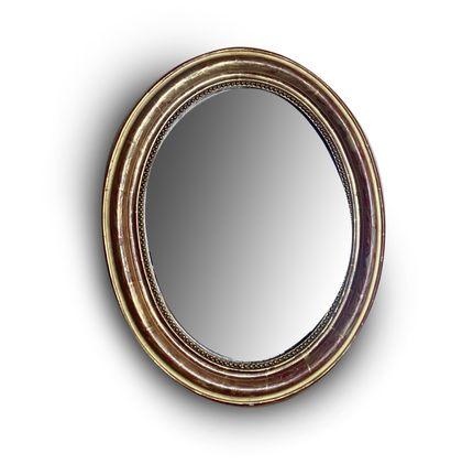 Miroir ovale En bois doré au décor incisé...