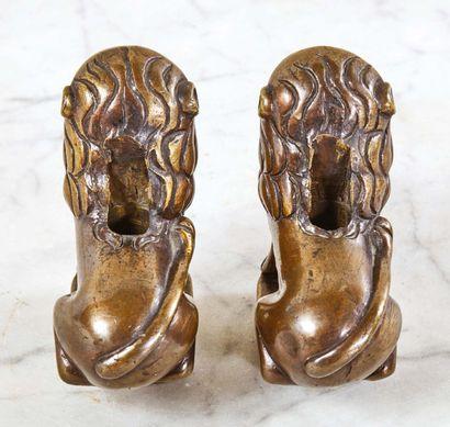 Paire de lions en bronze, supports. Ils sont accroupis sur une terrasse moulurée...