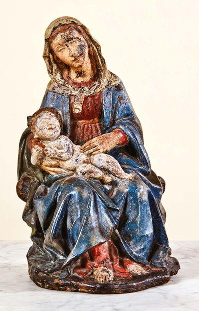 Vierge à l'Enfant en terre cuite polychromée. Marie est assise, portant l'Enfant...