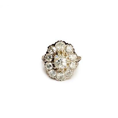 Bague marguerite en or jaune 18K (750), ornée d'un diamant central, de taille ancienne...