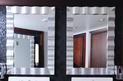 Miroir de forme mouvementée en bois argenté....