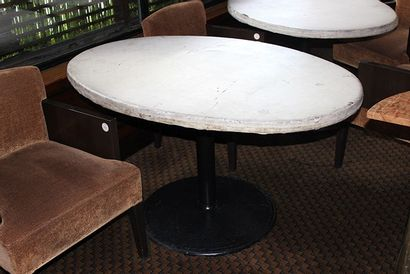 Huit tables ovales à piètement en fonte laquée...