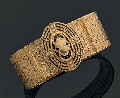BRACELET souple, coulissant, en or jaune 18 K ciselé, stylisant une ceinture. Le...