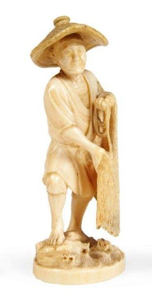 OKIMONO en ivoire, pêcheur debout tenant...