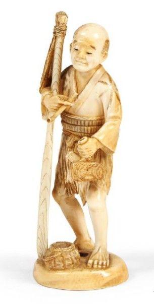 OKIMONO en ivoire à patine jaune, pêcheur...