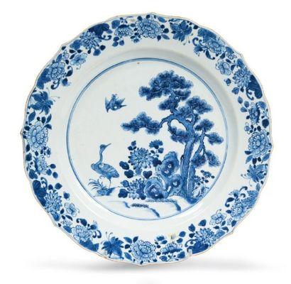 PLAT festonné en porcelaine décorée en bleu...